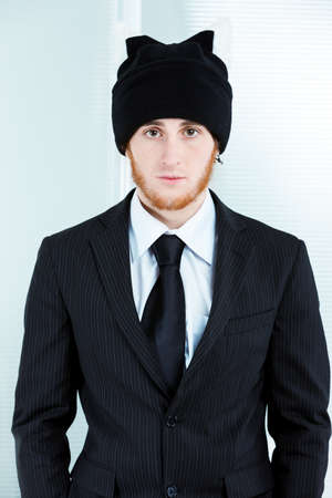 Strange businessman wearing a knitted black cap with his suit and tie staring at the camera with a deadpan expression in an isolated portrait