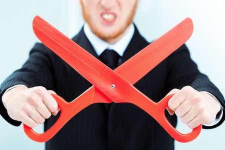 Mann mit dem harten Gesicht , der den Anzug hält große rote offene Scheren hält Standard-Bild