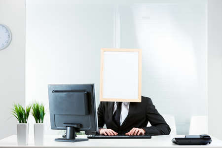 Businessman with a blank white sign in a frame for a face sitting at his desk in the office typing on a desktop computer in a conceptual image