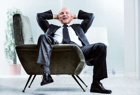 Businessman sitting relaxing and de-stressing in a comfortable armchair with his leg draped over the side, hands behind his neck, eyes closed and a happy smile