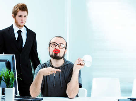 An effeminate male office worker wearing bright red lipstick sitting at his desk simpering watched in disgust by a colleague in a smart suit and tie