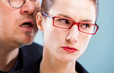 man on woman harassment concept with a man murmuring and whispering in woman's ear