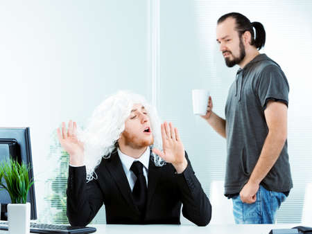 Affected narcissistic young businessman wearing a suit and white wig in the office gesturing with his hands watched with disgust by a casual co-worker
