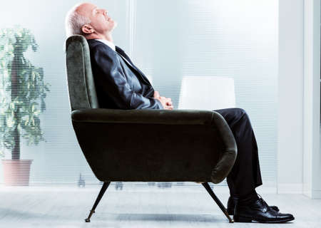 Tired businessman taking a moment to relax sitting in a comfortable armchair with his head back and eyes closed in a side view