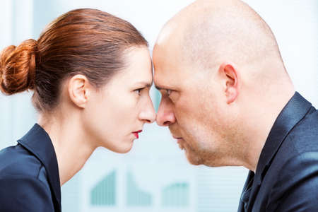 Businessman vs businesswoman head to head office confrontation