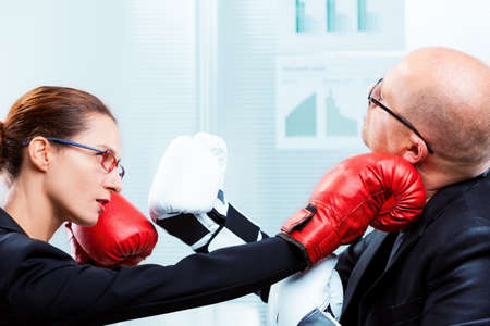 box match between a businesswoman and a business man - concept of man VS woman on the job Stock Photo