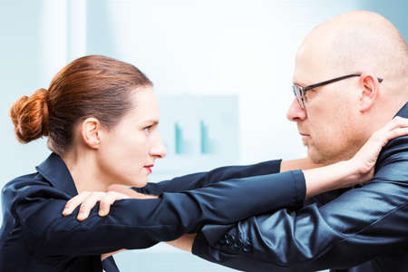 Businessman vs businesswoman face to face confrontation in office Stock Photo
