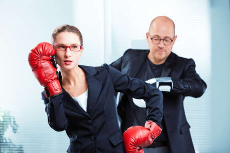 Woman talking on phone with boxing gloves while man standing behind her back looking at watch in office