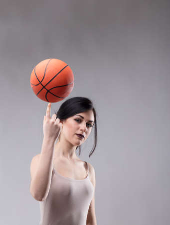 Attractive sporty young woman balancing a basketball on her fingertip while looking at the camera with a serious thoughtful expression on a grey studio background