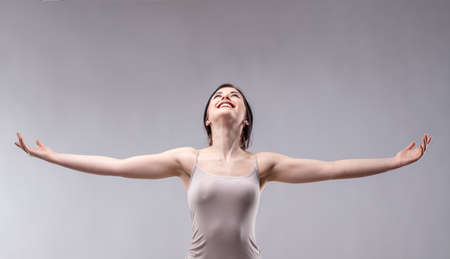 Happy attractive young woman rejoicing looking up with outstretched arms and a joyful vivacious smile to copy space on a grey background