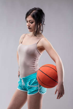 Sexy jaunty attractive young woman in skimpy blue shorts posing with a basketball on her hip over a grey studio background and looking down