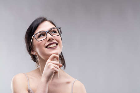 Happy attractive young woman wearing glasses standing daydreaming looking up with a beaming smile of pleasure with lateral copy space on grey