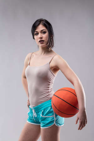 Sexy jaunty attractive young woman in skimpy blue shorts posing with a basketball on her hip over a grey studio background