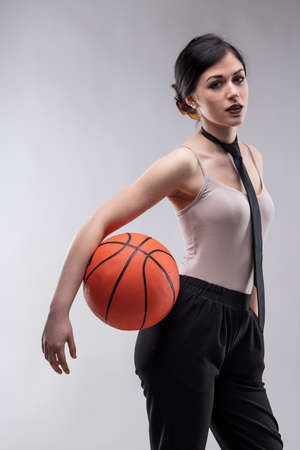 Seductive young brunette woman with dark lipstick standing with orange basketball and looking at camera