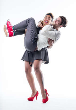 Young cheerful woman lifting man up against white background Stock Photo