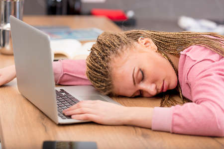 Exhausted attractive young woman asleep at her laptop computer collapsed over a kitchen counter at home with her eyes closed and serene expression Stock Photo