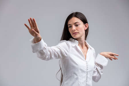 Imperious haughty woman flicking her hand in disdain with a look of supercilious scorn isolated on white Stock Photo