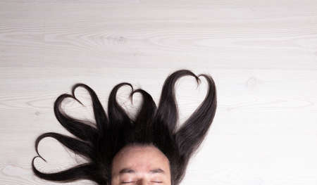 man laying with closed eyes and locks of hair reaching out of his head in shape of four hearts