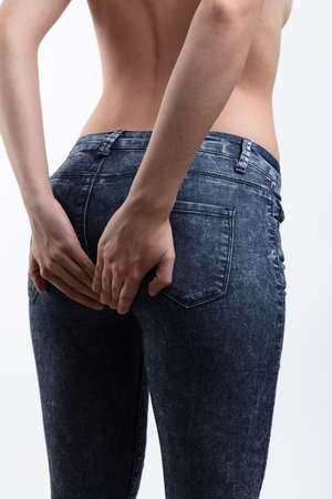 A young, topless caucasian woman holding her buttocks in denim jeans on a white background with copy space. Stock Photo