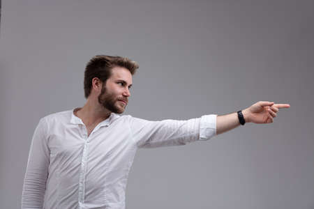 Attractive bearded man pointing to the side with an outstretched arm isolated on grey with copy space