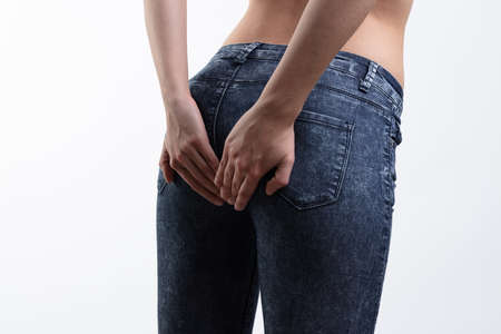 A young, topless caucasian woman holding her buttocks in denim jeans on a white background with copy space. Stock fotó