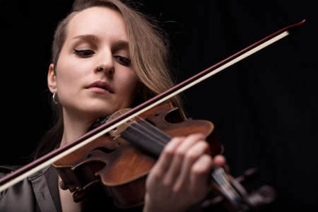 serious and concentrated violin player - portrait of a woman on black background playing strings