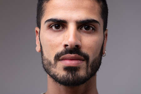 Close up portrait of young serious bearded man wearing earing