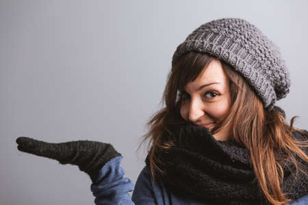 Playful attractive young woman in a warm woolly winter outfit holding out her empty palm with a happy smile for product placement or presentation