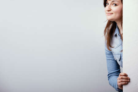 Cheeky young woman peering around a white sign with a mischievous grin over a white studio background with copy space Imagens