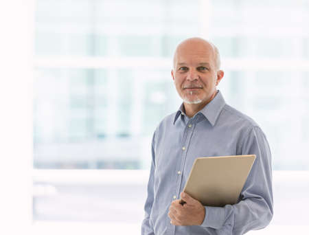 Business man holding laptop in one arm while facing the camera. Imagens