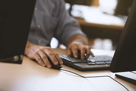Business mans hands typing away on computer keyboard.