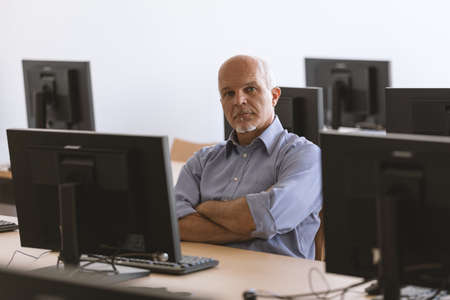 Business man looking at camera with arms folded while sitting at desktop computer in classroom setting. Imagens