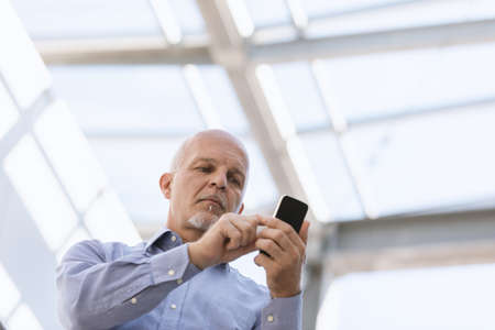 Low angle view of Business man texting on his mobile device. Imagens