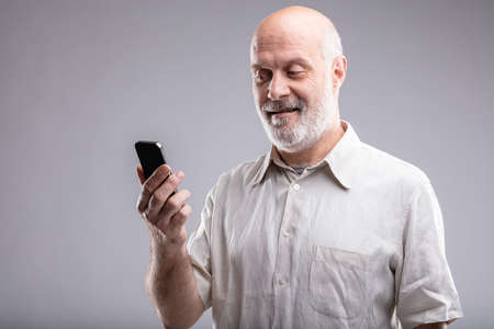 mature man looking satisfied his smartphone and the internet of things