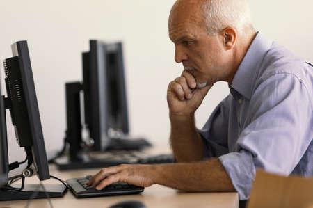 Profile view of Business man working away at desktop computer.