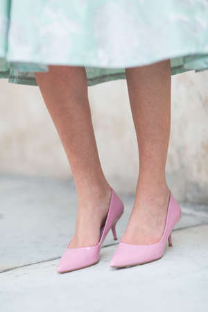 Woman wearing stylish pink high-heeled formal court shoes and a green dress standing against an exterior wall in a low angle view of her feet Imagens
