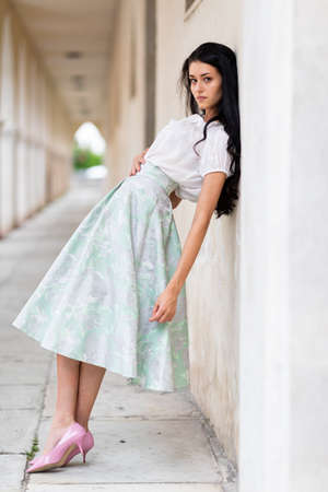 Beautiful slender stylish woman wearing pink high heel shoes and a full gathered green skirt leaning on a wall in a covered historical walkway looking thoughtfully at the camera Imagens