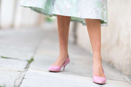 Stylish woman with shapely legs wearing pink stiletto court shoes standing on an urban sidewalk in a low angle view in a formal green dress Imagens
