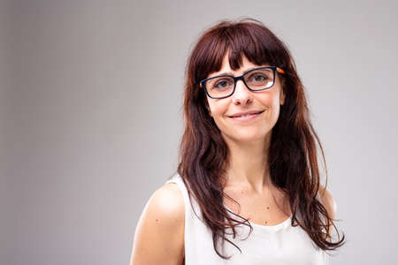 Smiling friendly woman with long brown hair wearing glasses looking at the camera over grey with copy space to the side