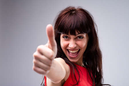 Happy enthusiastic attractive dark haired woman giving a thumbs up gesture of success and approval with focus to her face Imagens
