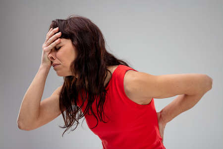 Miserable woman with backache holding her head and lower back in pain as she stoops forwards in a side view on grey Imagens