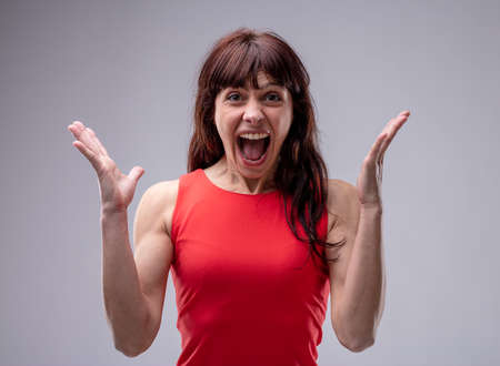 Surprised enthusiastic woman cheering and gesturing with her hands with an elated expression, upper body isolated on grey