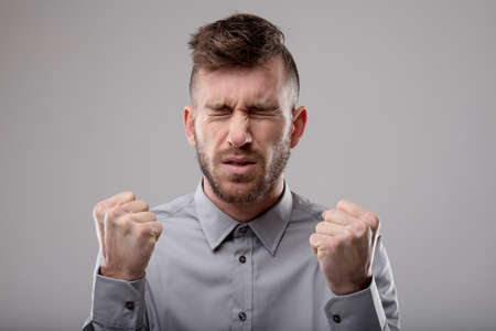 Ein Mann, der tief in der Konzentration ist, kniff die Augen zusammen und runzelte die Stirn, während er seine auf Grau isolierten Fäuste ballte