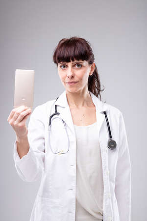 Serious female doctor holding up a mobile phone in her hand as she stands in a white lab coat looking intently at the viewer