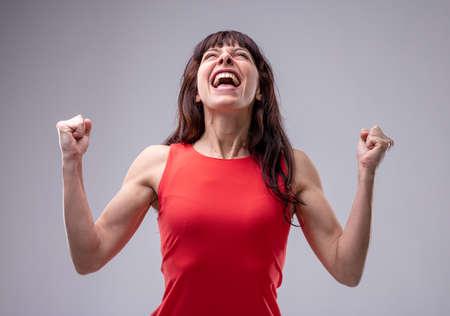 Aufgeregte Frau, die mit geballten Fäusten feiert und ihren Kopf zurückwirft und ihre auf Grau isolierte Freude schreit