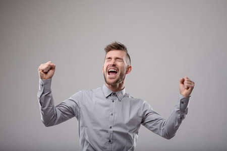 Elated man celebrating and cheering a success while punching the air with his fists over a grey background