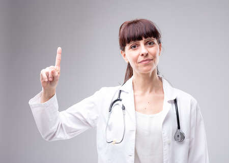 Smiling woman doctor or nurse with a stethoscope around her neck holding up a finger pointing up above her over a grey background Imagens