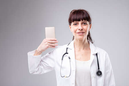 Smiling woman doctor holding up her mobile phone as she looks at the camera wearing a white lab coat and stethoscope Imagens