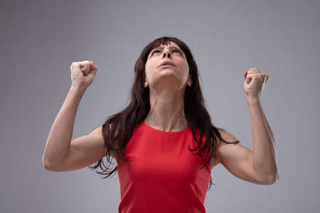Angry woman clenching her fists in frustration and looking up into the air with an imploring expression over grey