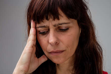 Worried woman with her hand to her head looking down and frowning with an anxious or pained expression in a close up cropped head shot